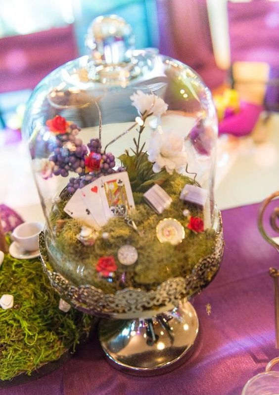 Alice in Wonderland inspired centerpiece with moss, flowers and cards