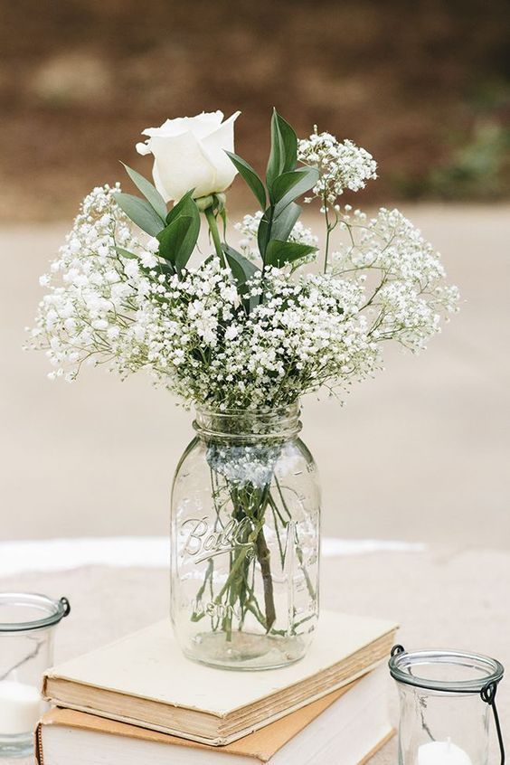 a stack of vintage books and a clear mason jar with a white floral arrangement