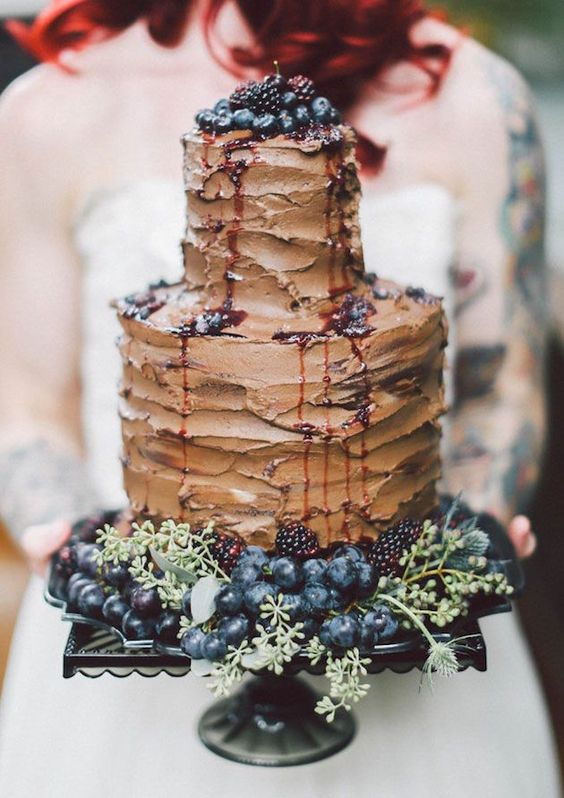 chocolate wedding cake topped with blackberry, blueberry and grapes