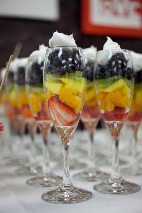 glasses with fruits and berries and whipped cream on top
