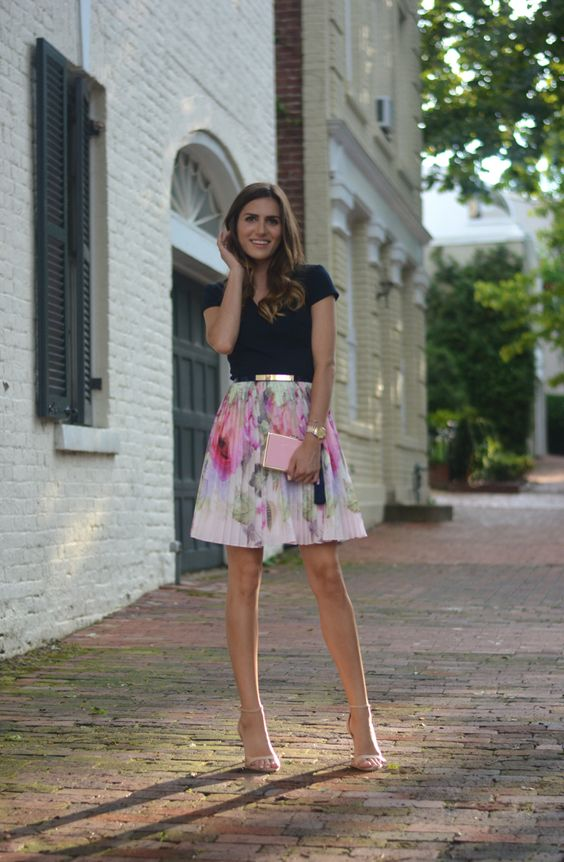 a black shirt, a floral pleated mini skirt, nude heels and a pink clutch