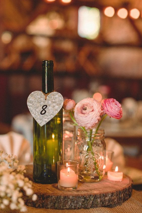 a vineyard centerpiece with a wine bottle, a mason jar as a vase and candles
