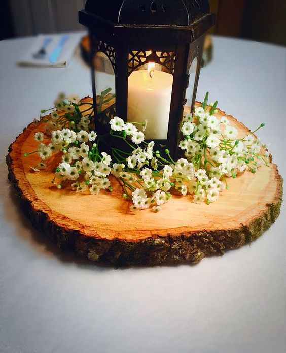a wood slice covered with wildflowers and a black candle lantern