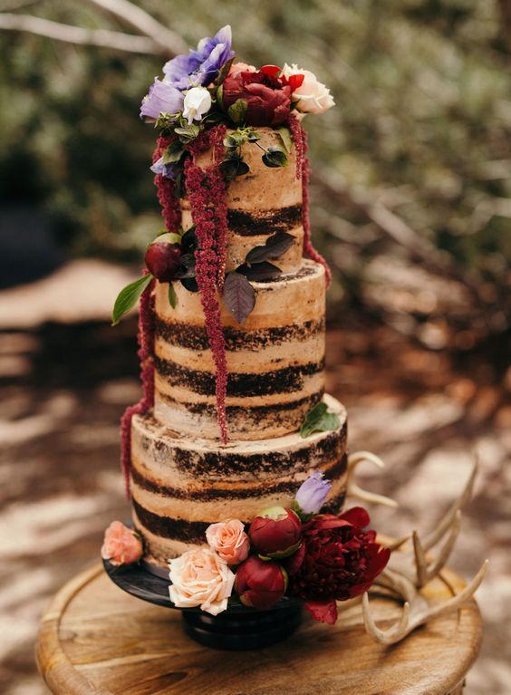 dark naked cake with red and purple flowers for a solstice wedding