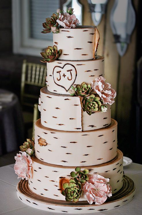 multi-tiered wedding cake topped with blooms and succulents
