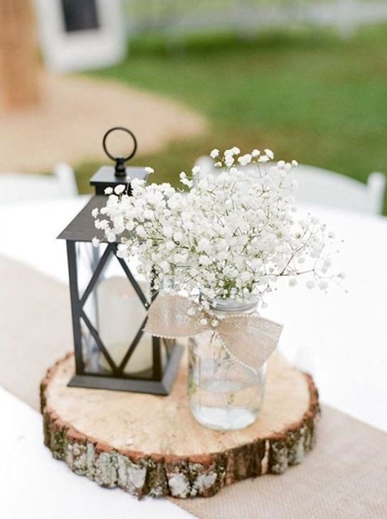 a wood slice with a candle lantern and a mason jar with baby's breath