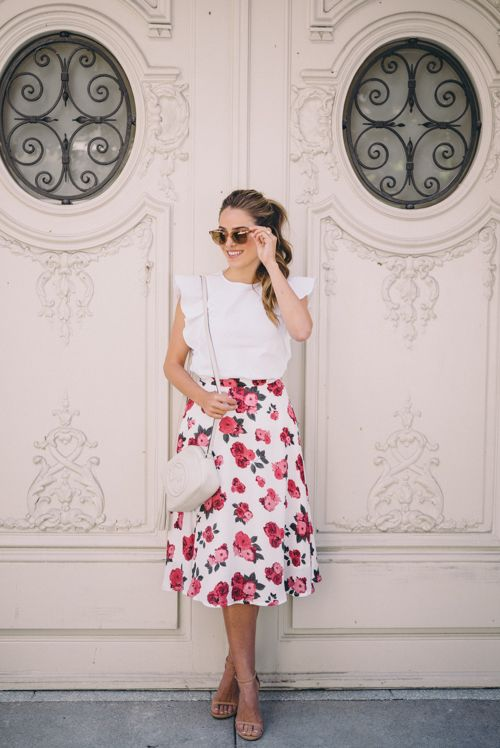 a pink floral printed skirt, a white ruffled top and nude heels