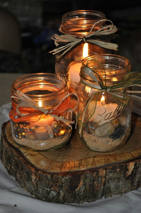three mason jars with sand and pebbles plus candles inside for a coastal wedding