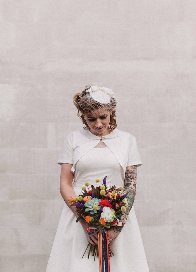 The bride was wearing a vintage tea-length wedding dress with a bolero and a birdcage veil