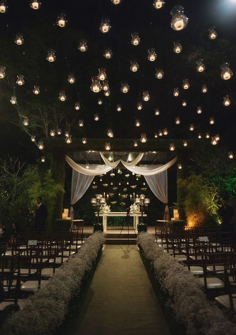 floating candle holders over the whole space and on the wedding arch
