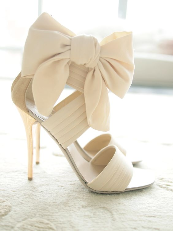 strappy cream high heels with oversized ribbon bows on the ankles
