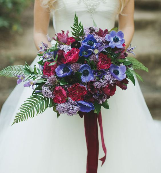 violet and fuchsia flowers and green leaves make this bouquet eye-catching