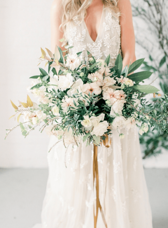 The bride was carrying an organic bouquet full of greenery and neutral flowers
