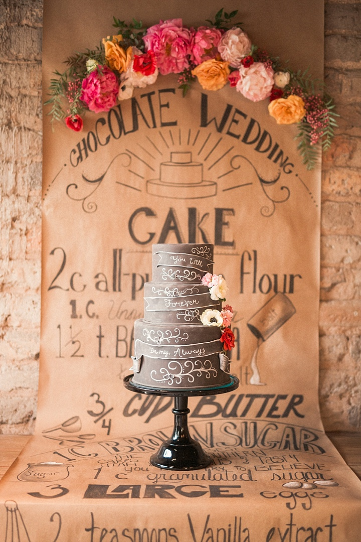 The wedding cake with chalkboard decor and some blooms