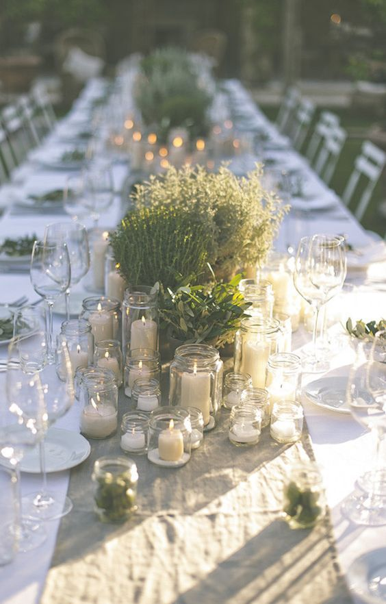 simple potted plants and greenery with lots of candles can comprise great centerpieces