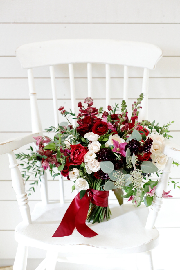 Amazing bridal bouquet with white and red roses, burgundy blooms and textural greenery