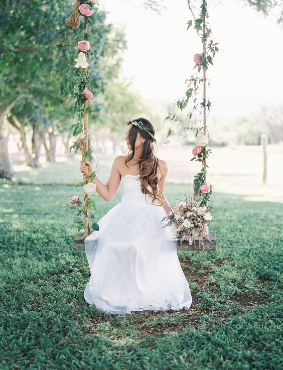 a cool swing decorated with leaves and pink blooms for bridal pics