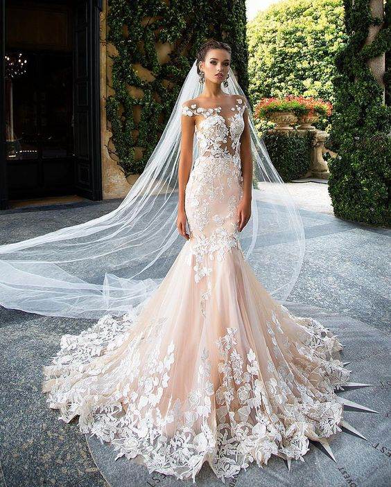 blush mermaid dress with an illusion bodice and white floral appliques over the whole gown