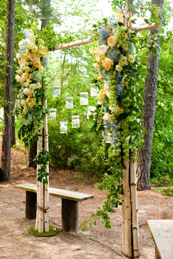 candle lanterns hanging on a birch and flower arch