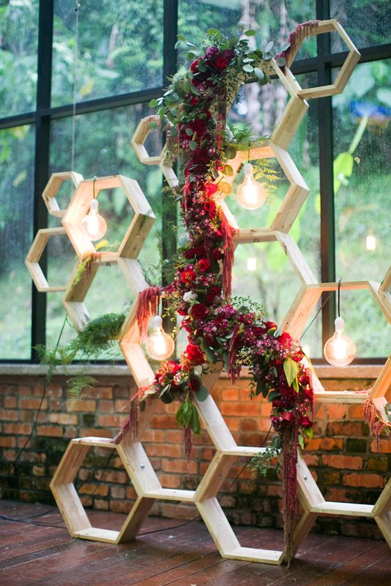 light-colored wooden hexagons with bulbs and burgundy roses and amaranthus