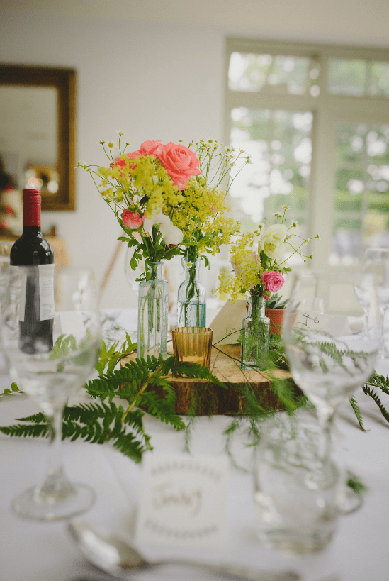 Apothecary bottles were gathered by the bride, flowers were grown by the groom's granddad
