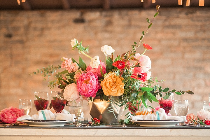 Bold pink and yellow floral centerpiece for accentuating the table