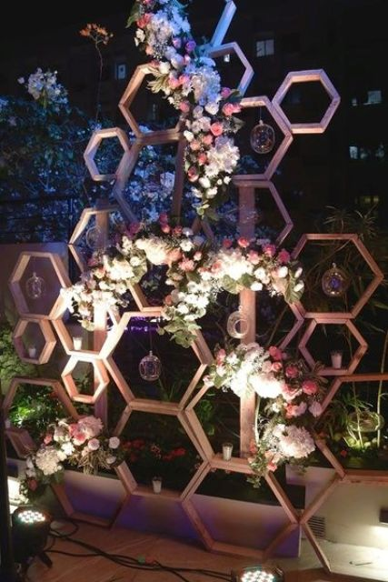 hexagon wedding backdrop with lush pink and white flowers and candle bubbles