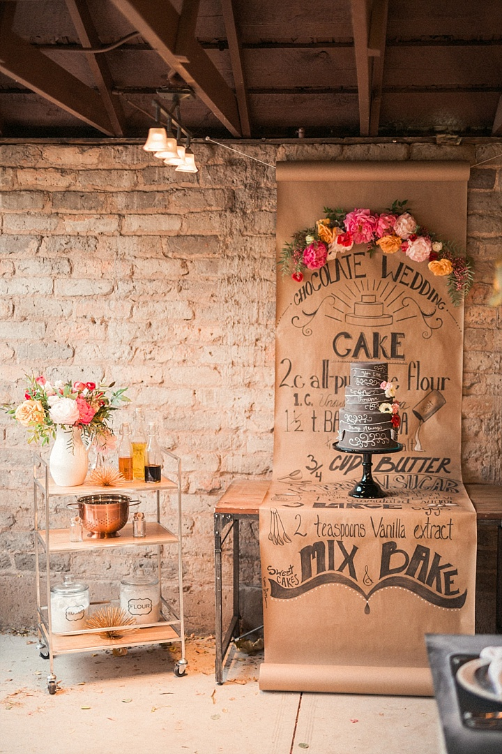 The cake table with a paper backdrop and cake's recipe written on it