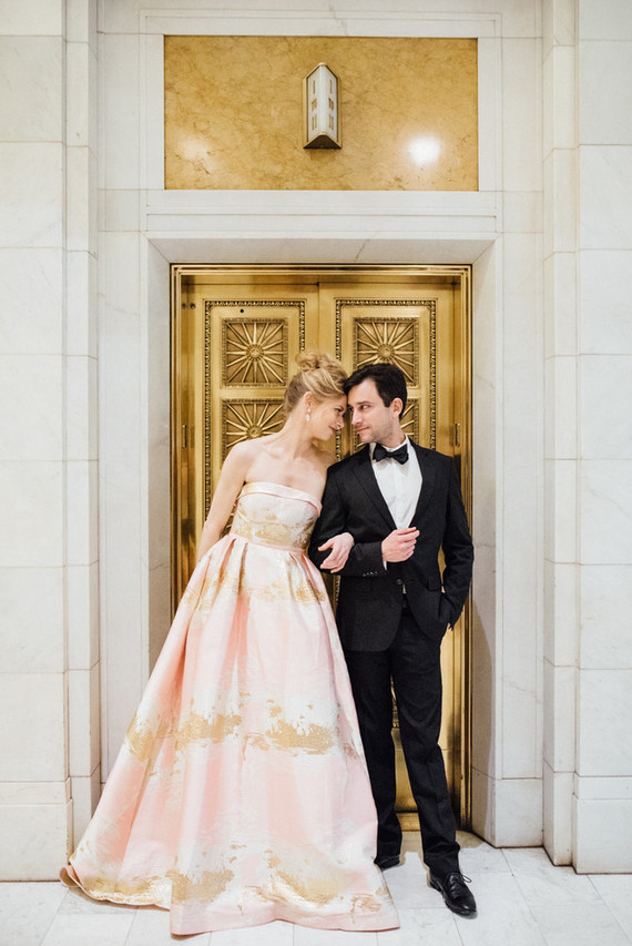 The groom was wearing a classic tux, and the bride was rocking a unique strapless pink and gold metallic wedding dress