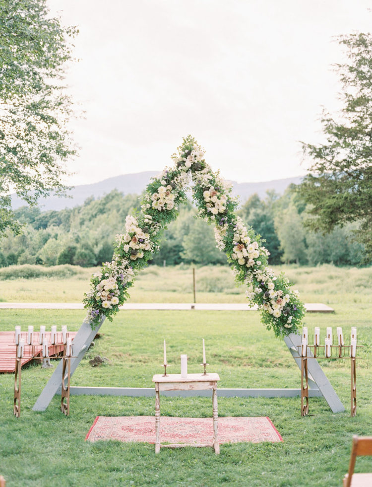 The wedding arch with all the florals by The Green Cottage and all the candles