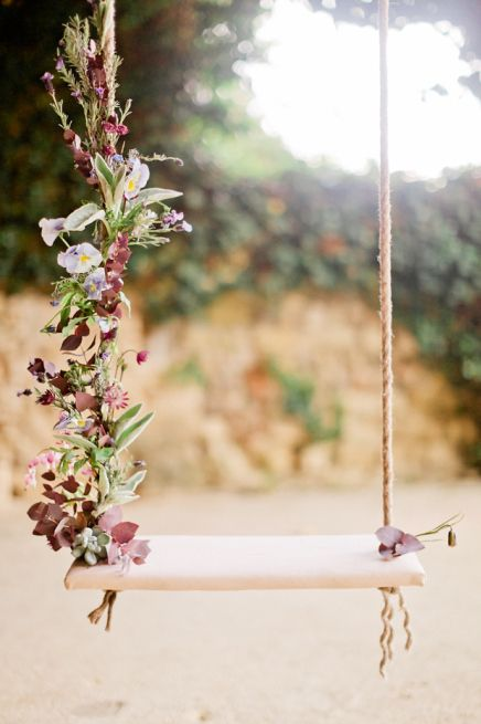 06 a gorgeous swing with one side decorated with greenery and flowers
