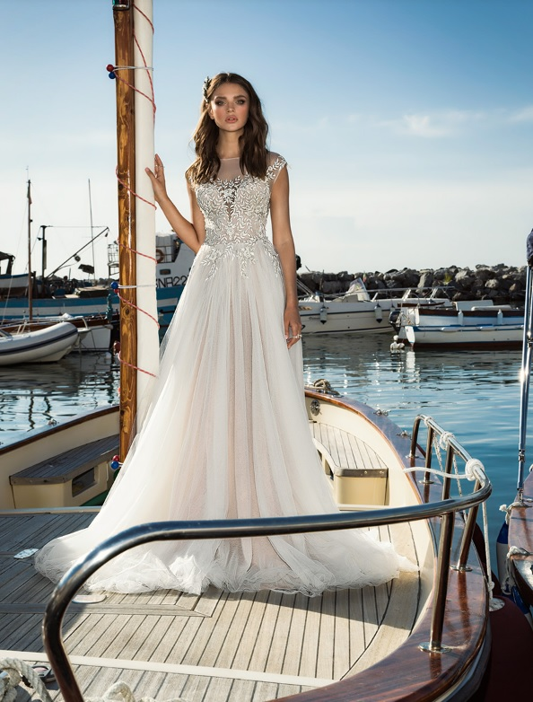 illusion neckline wedding dress with a lace applique bodice and a flowy skirt