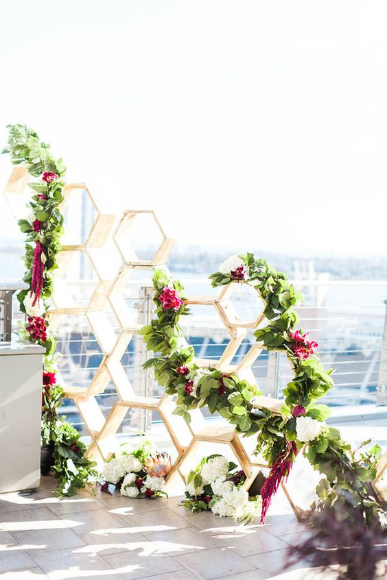 modern hexagon wedding backdrop with lush greenery and fuchsia blooms