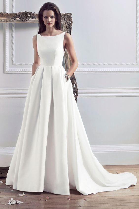 modern plain bateau neckline wedding dress with a pleated skirt and pockets