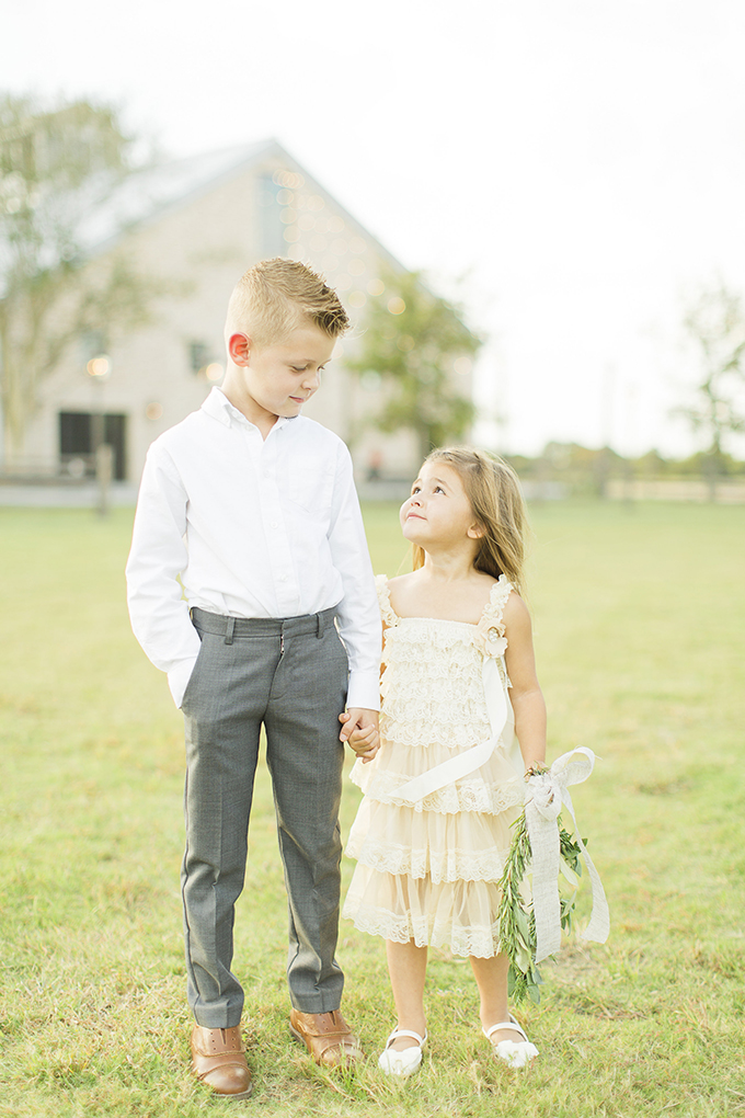 The little flower girl in her blush ruffle dress and a ring bearer in a white shirt and grey pants
