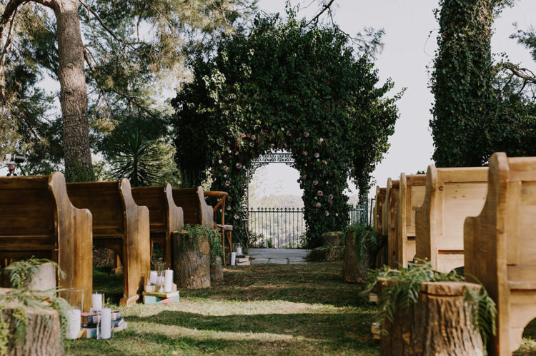 There was a garden ceremony with a stunning iron gazebo covered with greenery and rustic aisle decor