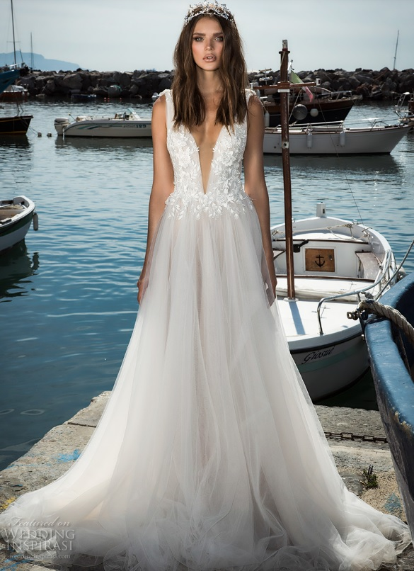 a white plunging neckline gown with lace appliques and a flowy skirt