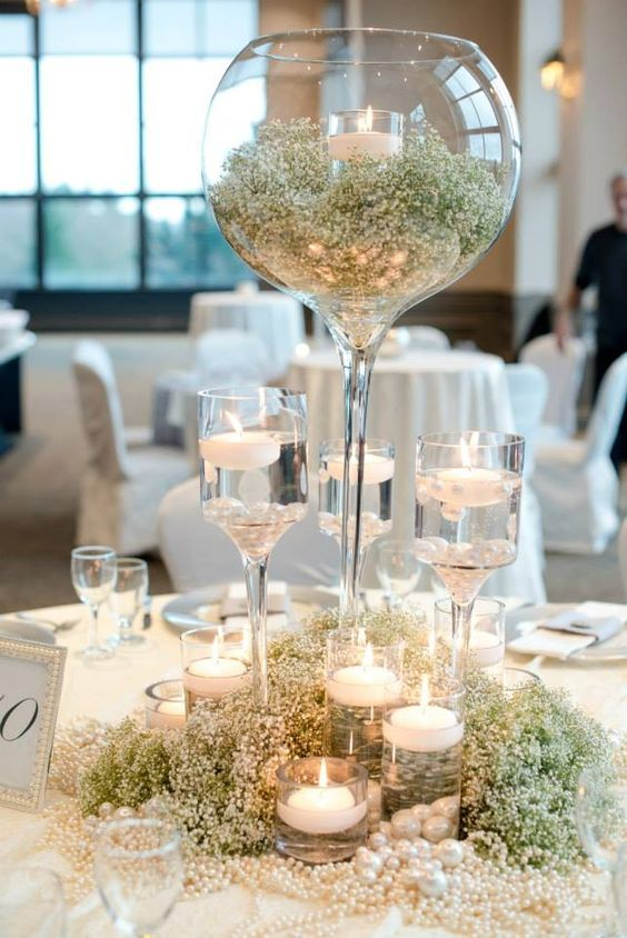 an oversized glass with baby's breath and a candle holder, baby's breatj and pearls to cover the table and candles