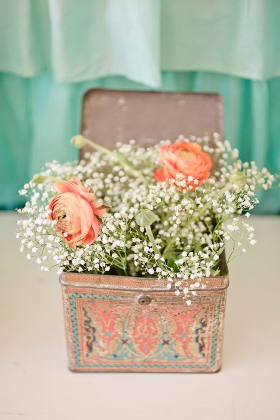 a vintage tin box with baby's breath and orange blooms
