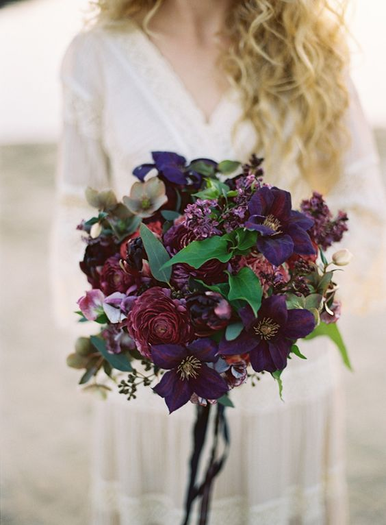 dark burgundy and purple moody bridal bouquet refreshed with green leaves