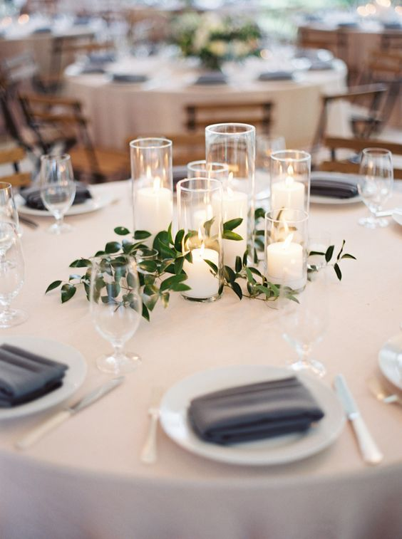 some candles with green leaves interwoven for a cute centerpiece