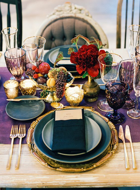 a decadent jewel tone tablescape with a deep purple table runner, purple goblets, gold flatware and a gold charger