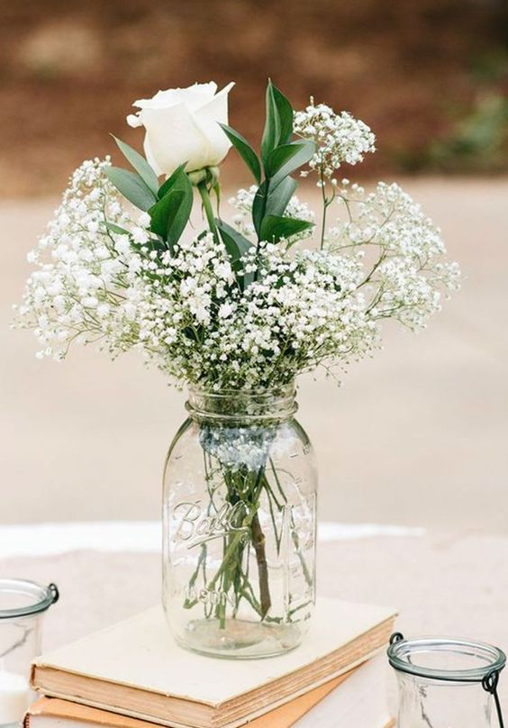 white roses, baby's breath in a jar on a stack of vintage books