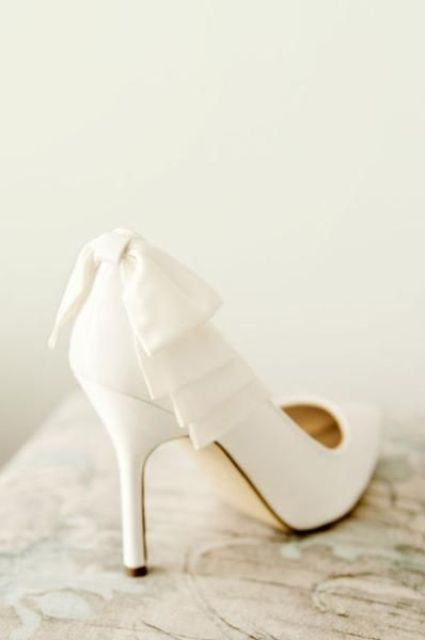 white wedding shoes with bows on the back