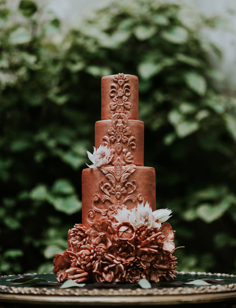 A copper wedidng cake with textural decor and edible flowers