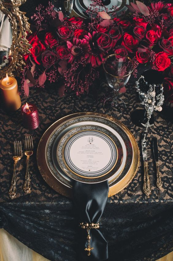 black and gold table setting with red roses decor, candles and black silk napkins