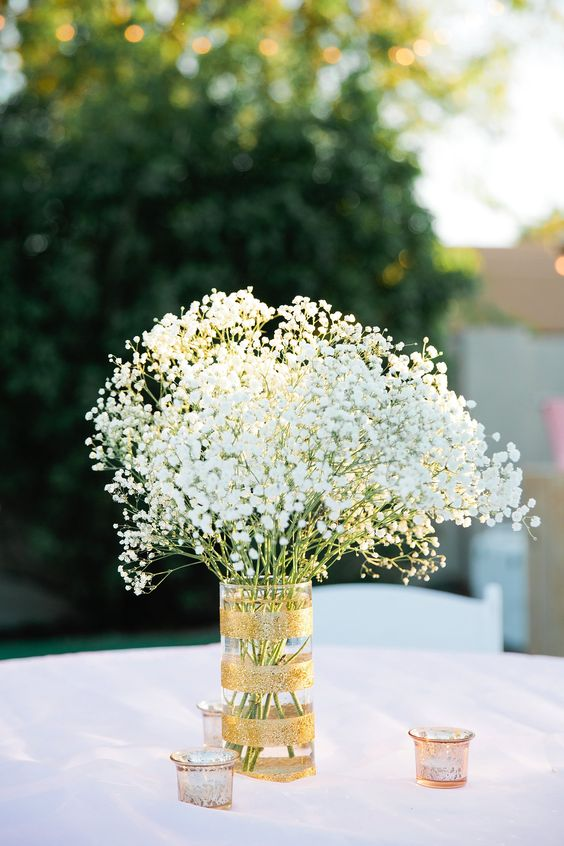 a gold glitter vase with baby's breath and candle holders around