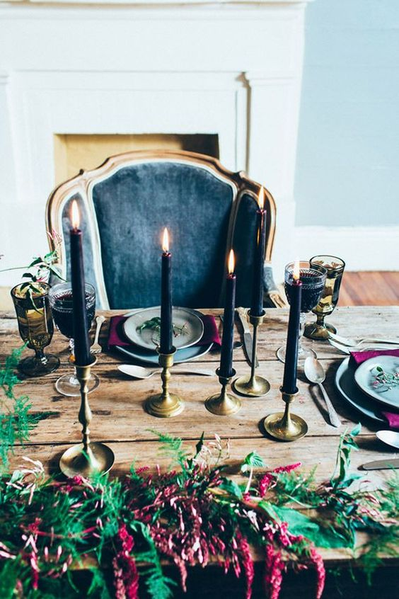 black candles in gold candle holders, exquisite glasses and moody florals for the refined tablescape