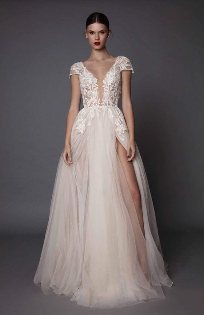 white plunging neckline wedding dress with cap sleeves and a flowy skirt with a side slit