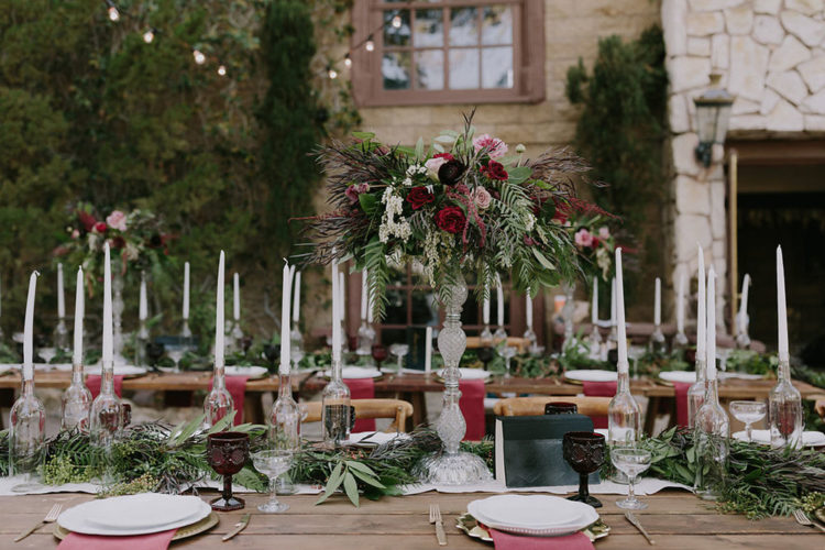 The wedding tablescape was adorned with dark florals and greenery, and lots of candles
